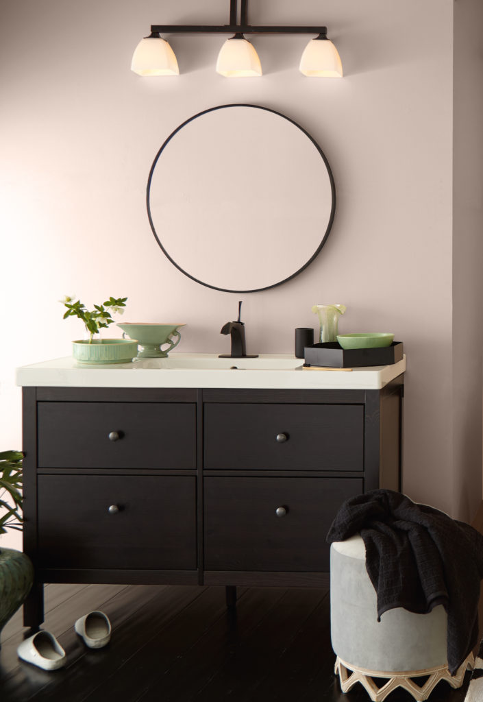 A light pink contemporary bathroom with a dark wood sink and with some jade green art deco glass decorative elements.
