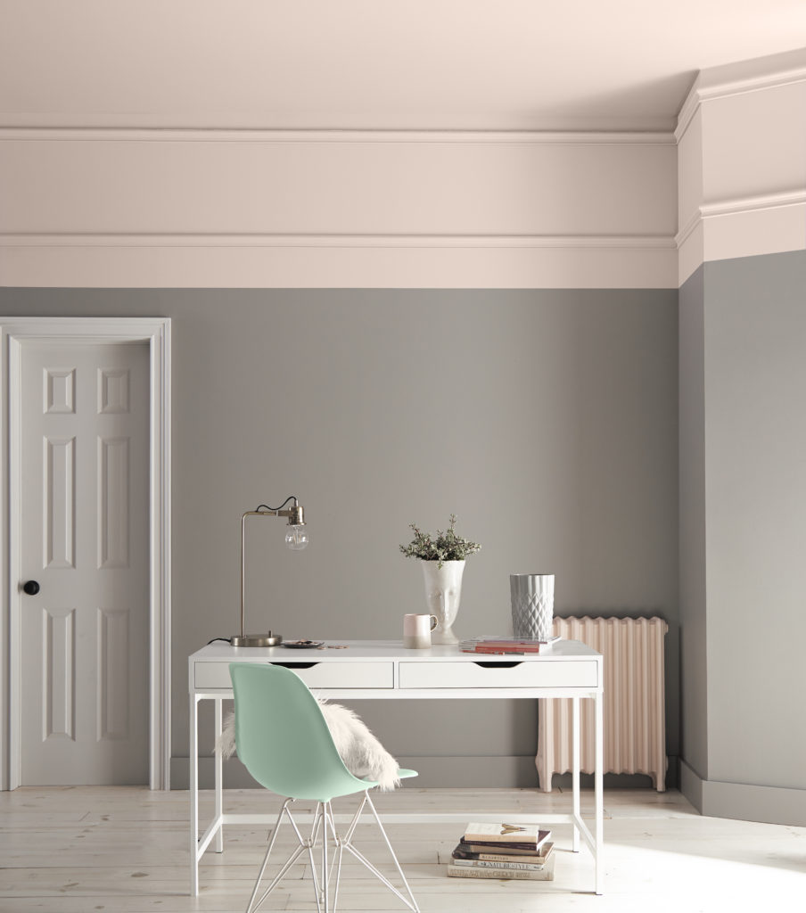 A modern home office placed in traditional room with beautiful ceiling molding.  A  wide stripe was painted along the ceiling for bigger impact.  The furniture is white and green which nicely coordinate with the gray walls and the pink border.