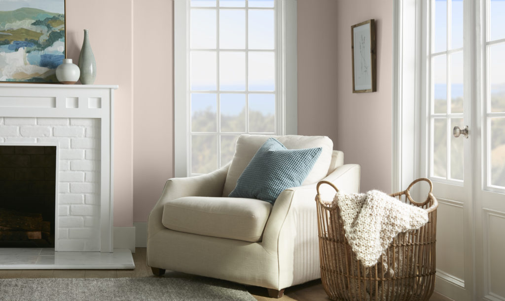 A reading corner placed in a room with a fireplace. There is a round and cushiony chair with a blue pillow to comfortably sit and read. Next to the chair there is a basket with a blanket.    Multiple window in the room allow for plenty of natural light to come into the room.