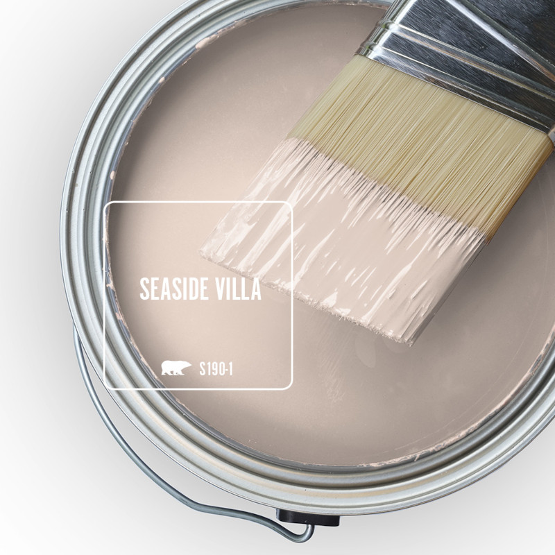 The top view of an open paint can, there is a haft dipped paint brush placed on top of the can, the color of the liquid paint is Seaside Villa.