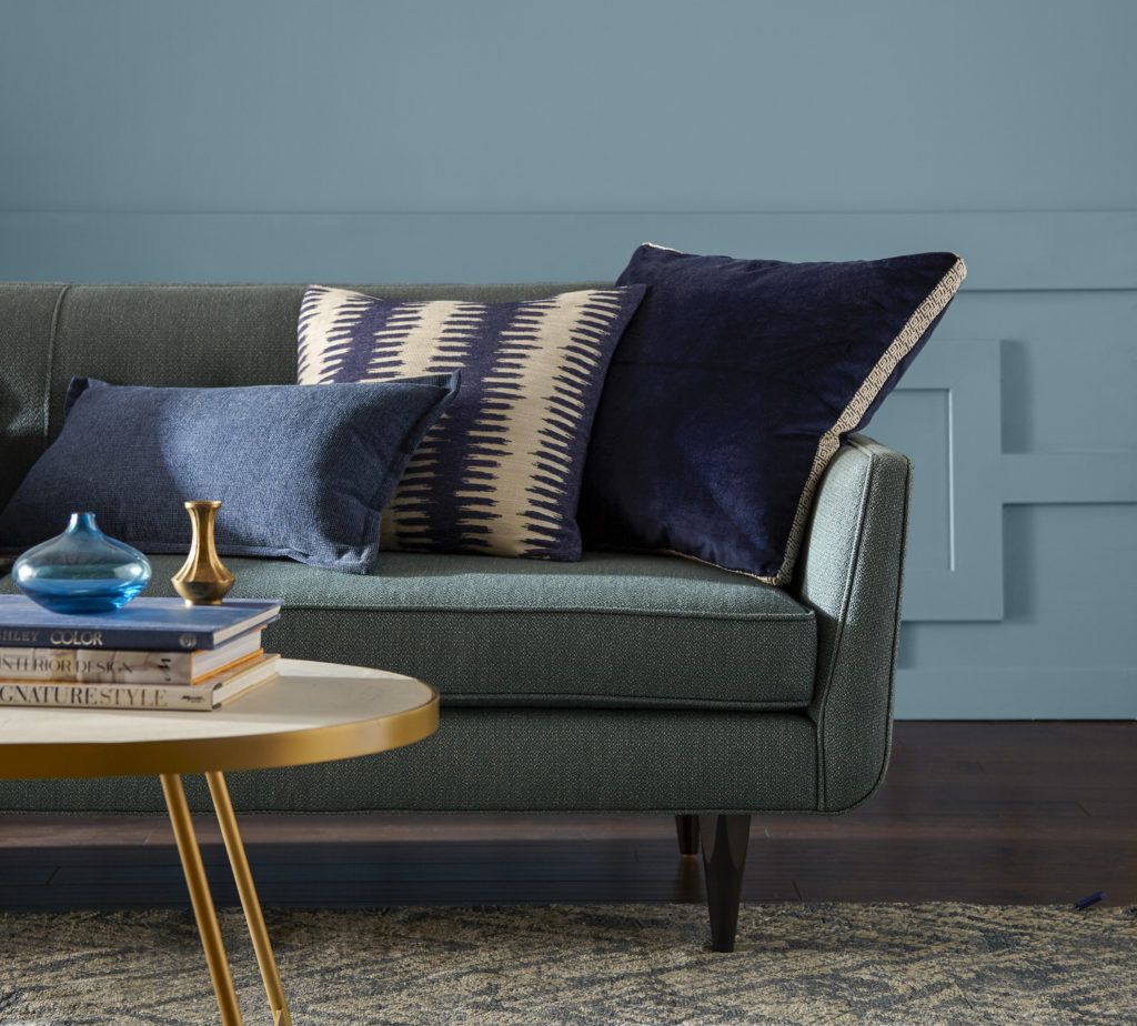 A mid-century modern living room with a gray sofa and blue and beige decorative pillows. The color on the wall is Voyage.