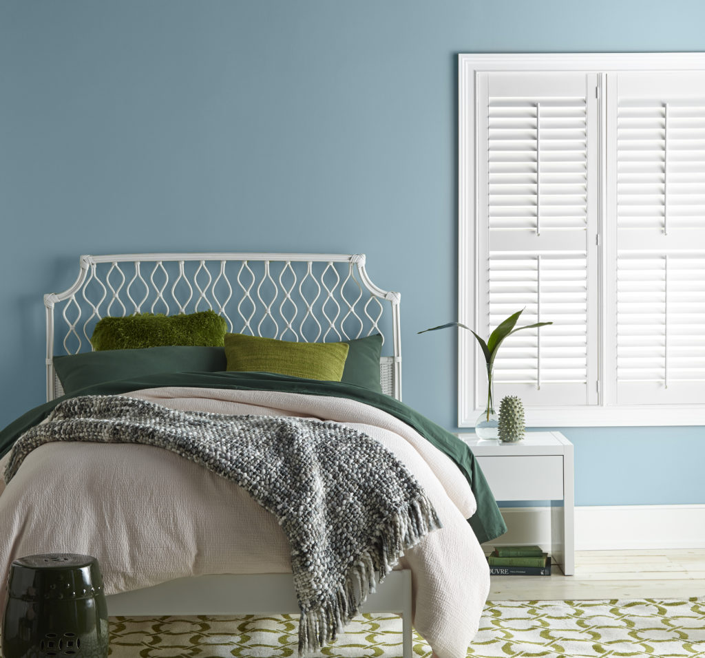 A beachy style bedroom featuring a blue wall, white window blinds. The white metal bed is dressed in white and variations of green tones on the bedding.