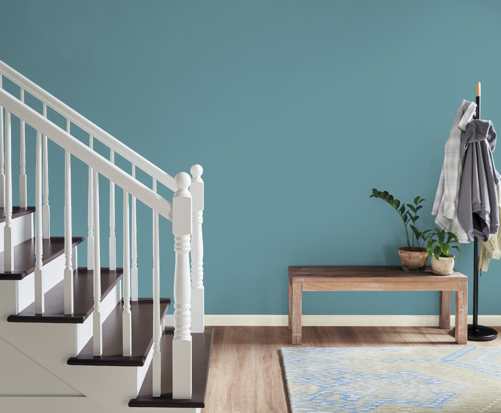 An entry area with an staircase, the color on the wall is a mid-tone blue called Voyage.  There is a rustic modern bench with two small potted plants.