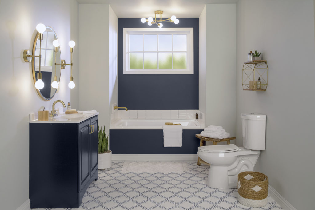 A completely DIY made-over bathroom.  The walls have been painted in a trendy light warm gray and an accent color called Starless Night.   The hardware and lighting fixtures have been replaced with an elegant brass finish. The floor has a completely new look with a stylish stenciled design.