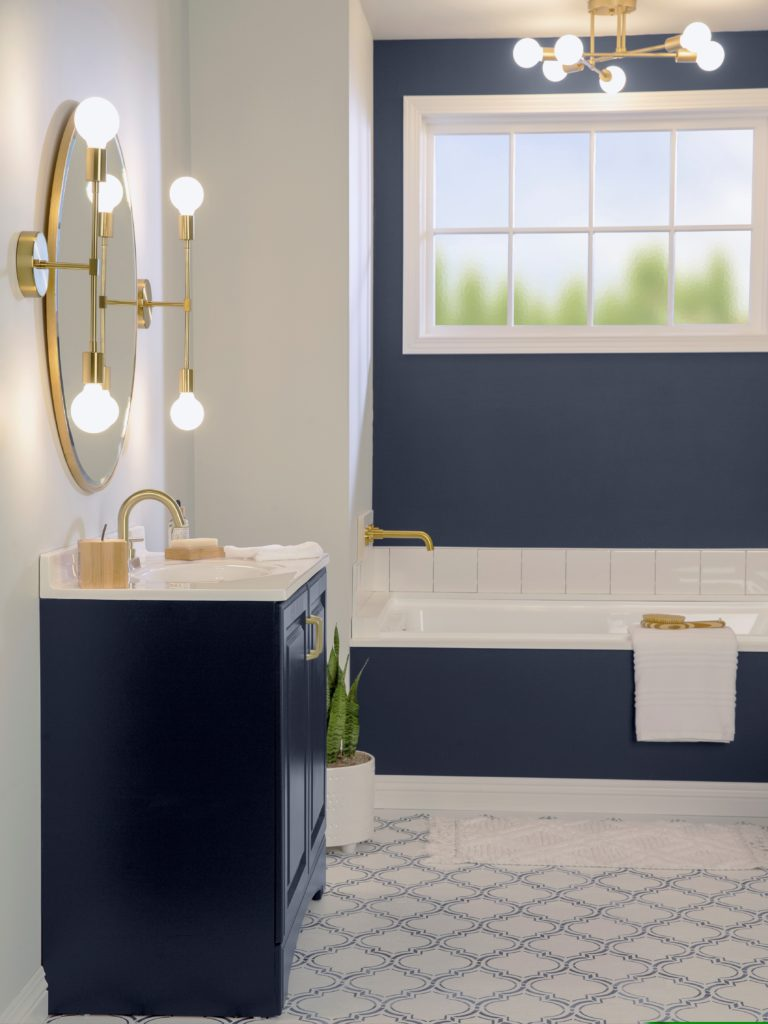 A beautiful bathroom that has been made over by painting the wall and vanity in a dark blue color.