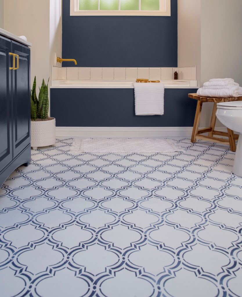 A close up shot of the newly designed bathroom floor. The design was created using a white paint color as the base and a dark navy color to create the stenciled design.