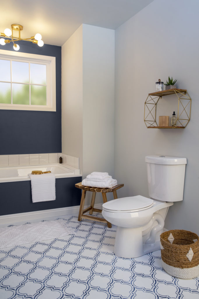 A vertical shot of the newly designed bathroom, focusing on the toilet side.  A fun and stylish shelf was added to that side of the wall to create visual interest and to display small plant, essential oils, and other small decorative items.