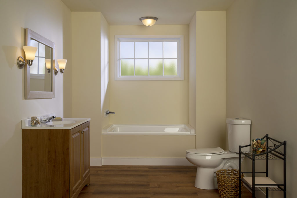 A not very exciting looking bathroom, the color of the wall is beige, the sink is made with a natural wood color and the hardware and lighting fixtures are very generic and bland looking.