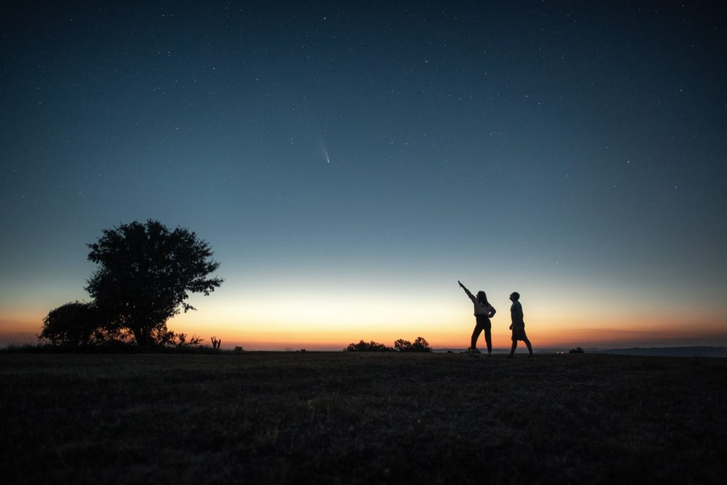 Silhouette of a young couple watching the Neowise comet  under the bright blue night sky after sunset.