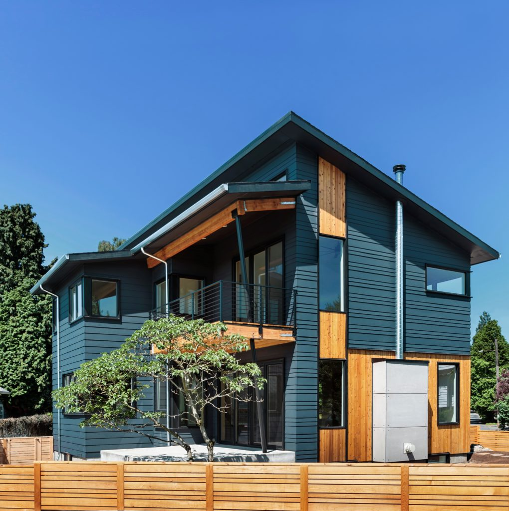 An Exterior Two Story Home with Wooden Mid Century Modern Look, the body of the house is painted in a dark blue color called Nocturne Blue.