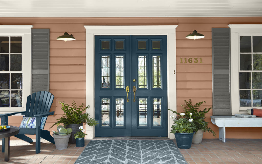 A house porch front featuring a blue door called with a dark color called Nocturne Blue.  The siding on the house body is painted in a warm terra cotta color called Canyon Dusk.  The shutters are painted in a dark yet understated gray color called Barnwood Gray.