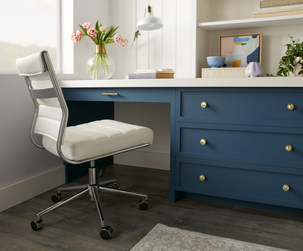 A trendy and stylish home office with super light purple and white walls, featuring a desk area painted in a dark color called Nocturne Blue.