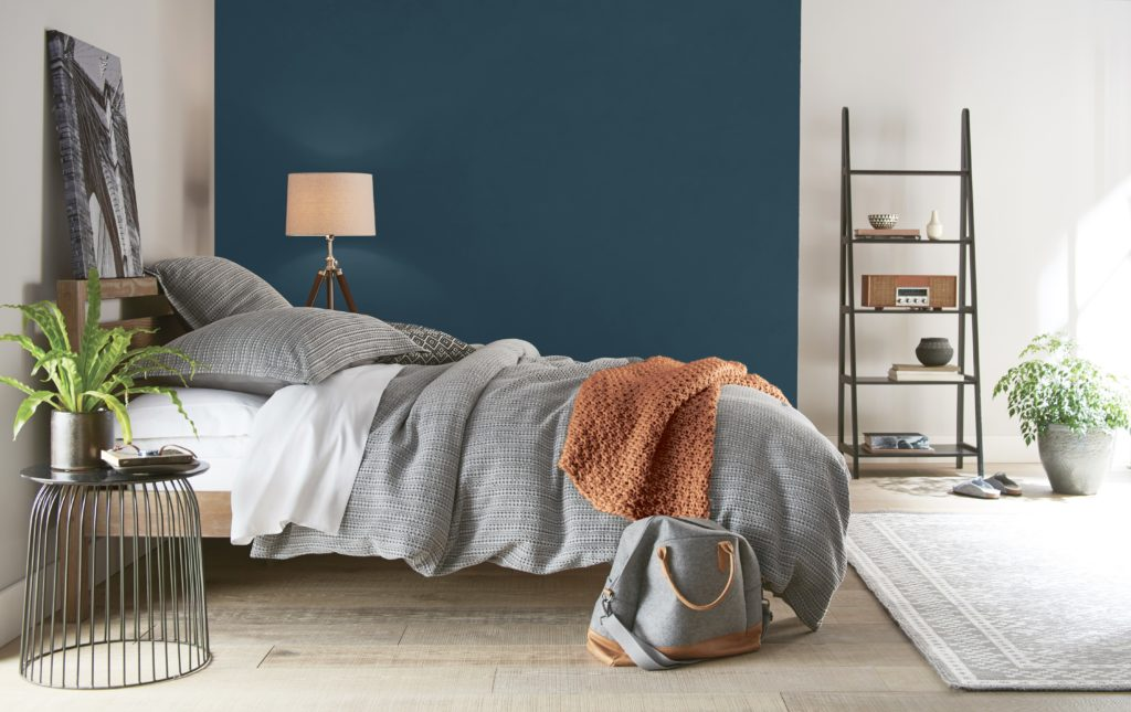 A urban modern bedroom featuring an accent wall painted in a dark blue color called Nocturne Blue