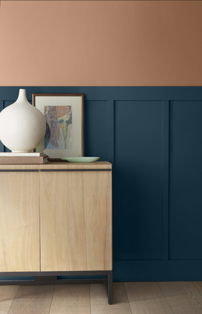 A feature wall painted in two different colors, the lower wall is a dark blue color called Nocturne Blue. The upper walls is painted in a terra cotta color called Canyon Dusk.
