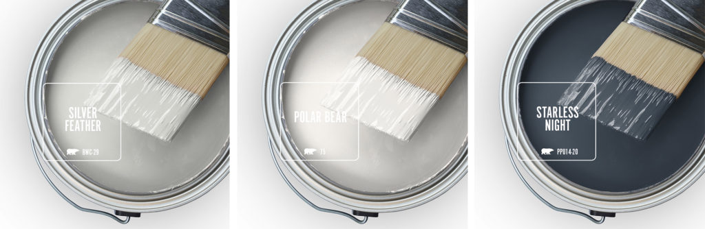 Three open paint cans with a half dipped brushes.  There is a light warm gray color, a white and a dark, almost black navy blue.