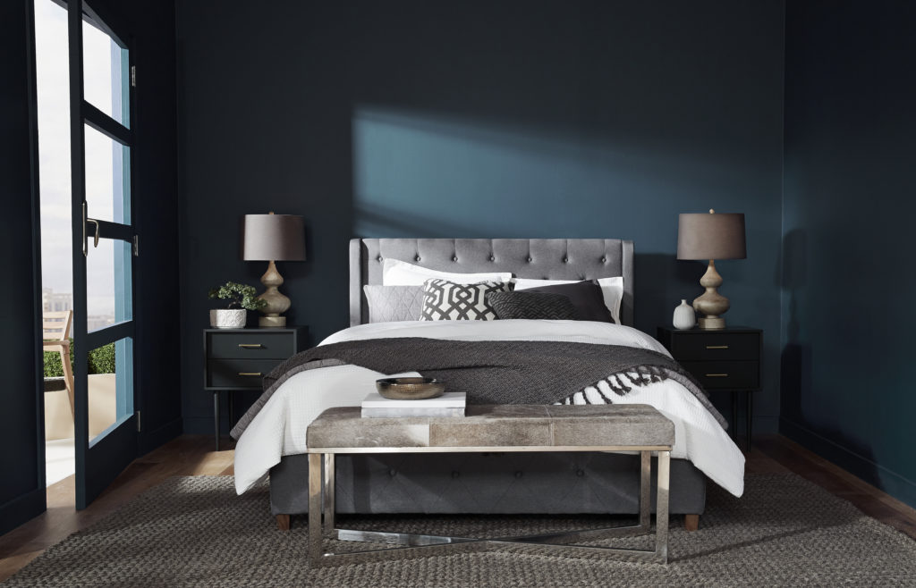 A moody, modern bedroom with an elegant upholstered gray bed. The walls are painted in a dark blue color called Nocturne Blue.