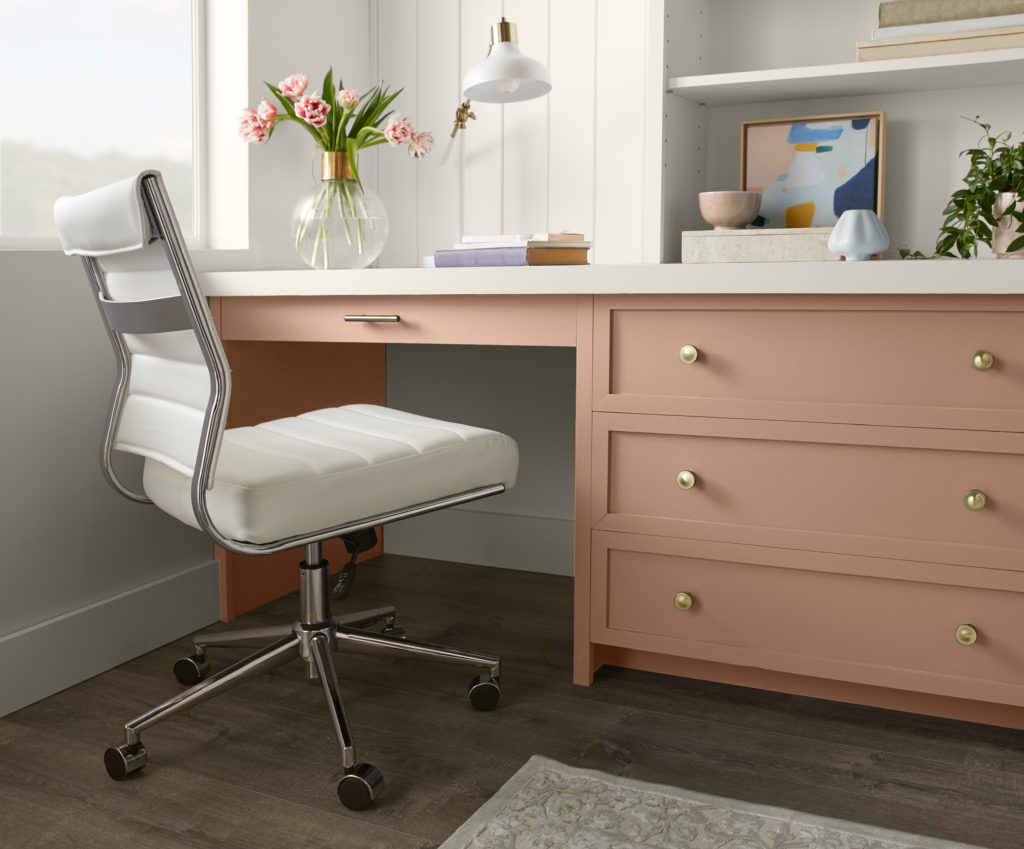 A built-in desk area in the corner of a room, featuring a terra cotta desk and bookshelves.  The walls on the room are white.  An adjustable white leather chair and some colorful accessories make up the rest of the office space.