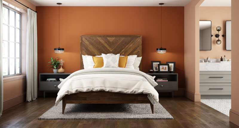 A large master bedroom and bathroom, both room are painted with orange tones.  The main color is a mid dusty terra cotta called Canyon Dusk and the accent color used on the headboard wall is called Maple Glaze.