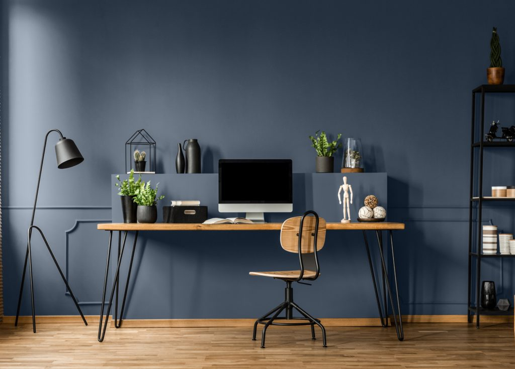Chair at wooden table with computer monitor and plants in dark blue and  spacious home office interior.