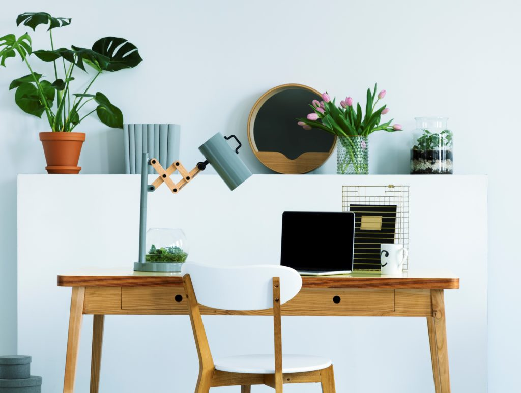A wall shelf with flowers and fresh plant, decor and books in white living room interior with study corner desk with lamp and mockup laptop.  The color in the wall is a light aqua called Beach Foam.