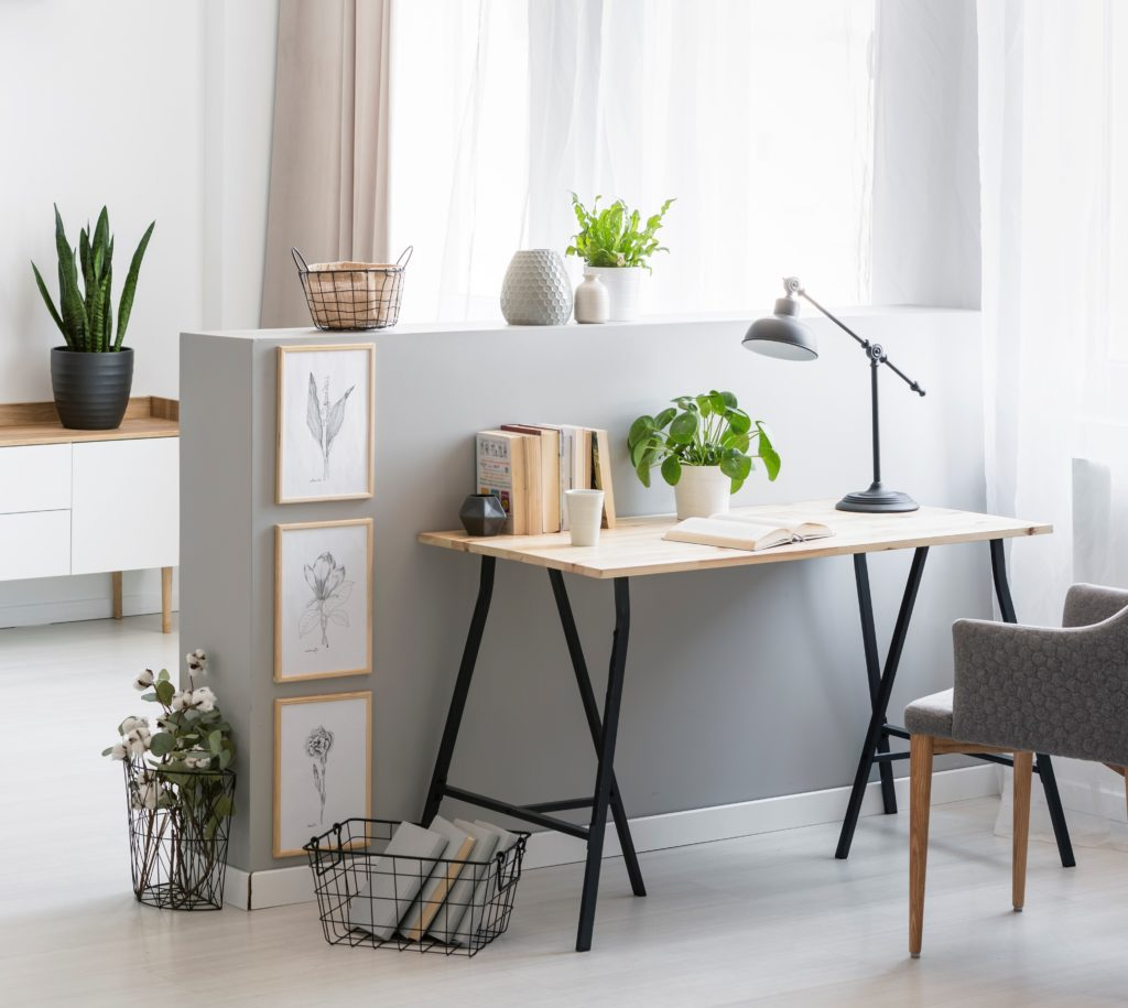 A short wall painted in a light gray paint color. A simple yet stylish home office area with a gray armchair at desk with plant and lamp.