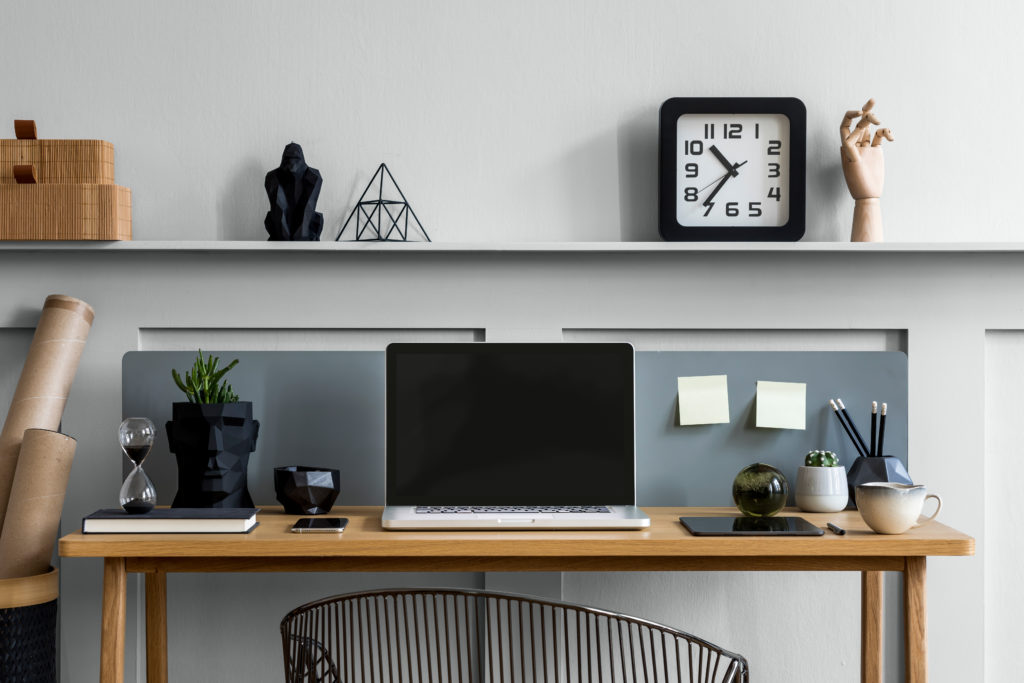 A light gray home office, the  composition on the wooden desk includes a display of  mocked up templates, office supplies and elegant accessories in modern concept.  The color used on the wall is called Platinum.