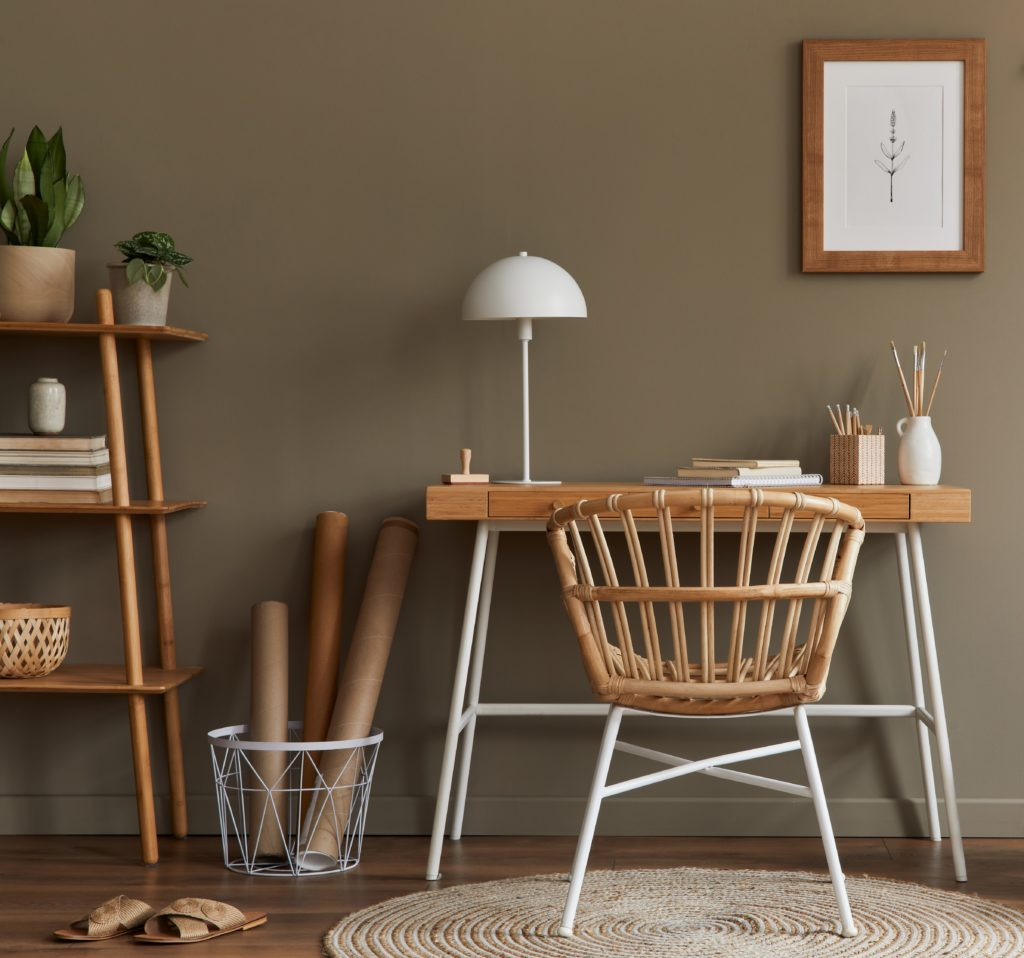 Stylish bohemian interior of home office space with wooden desk, office supplies, decoration and elegant personal accessories in home decor. The mod-to-dark brown color on the wall is called Light Truffle.