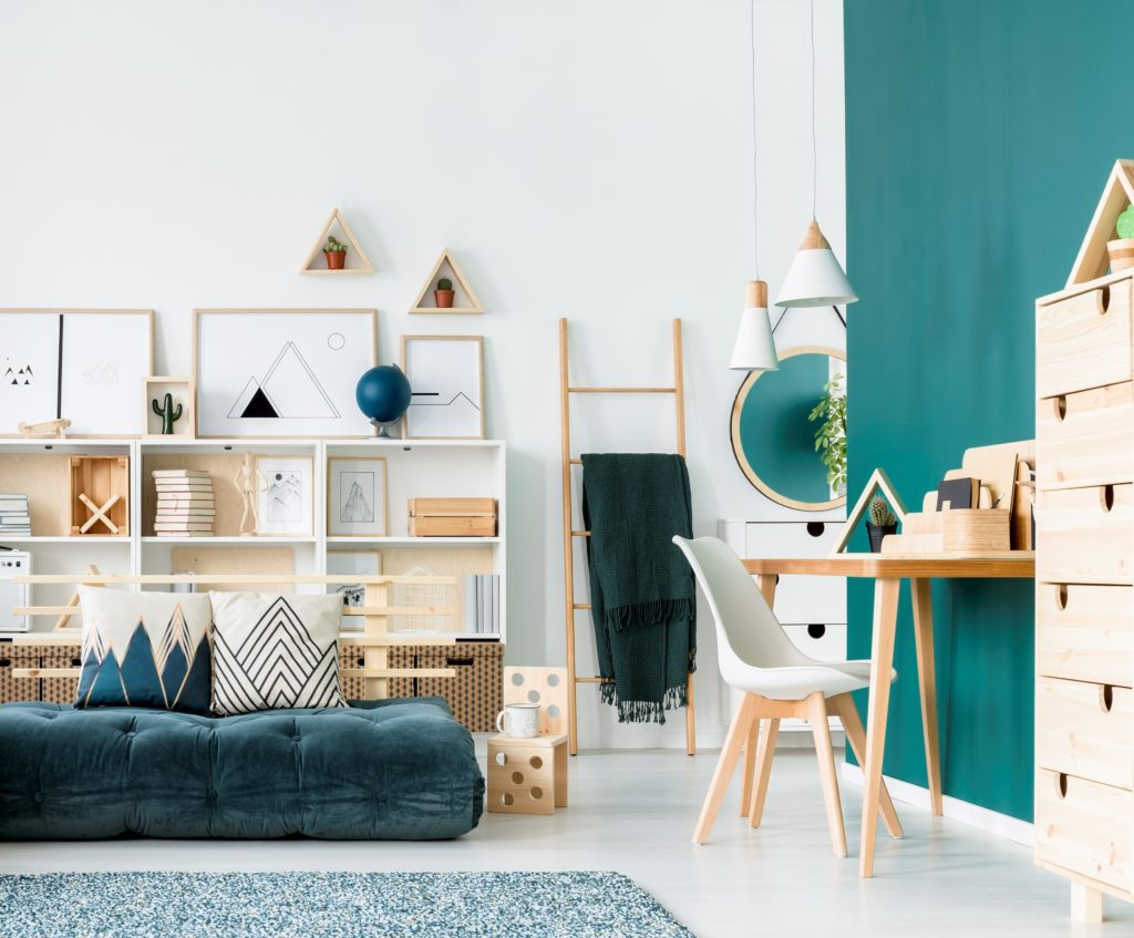 A speckled patterned carpet in white and turquoise colors, A unique bed and mattress in colorful living room interior , there is ao desk area with an accent wall painted in a turquoise color called Thai Teal.