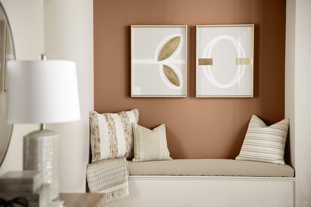 A cozy reading nook decorate with neutral pillows, the color of the walls is a light neutral called Almond Wisp. The accent color on the back wall of the nook is a darker caramel tone called Maple Glaze.