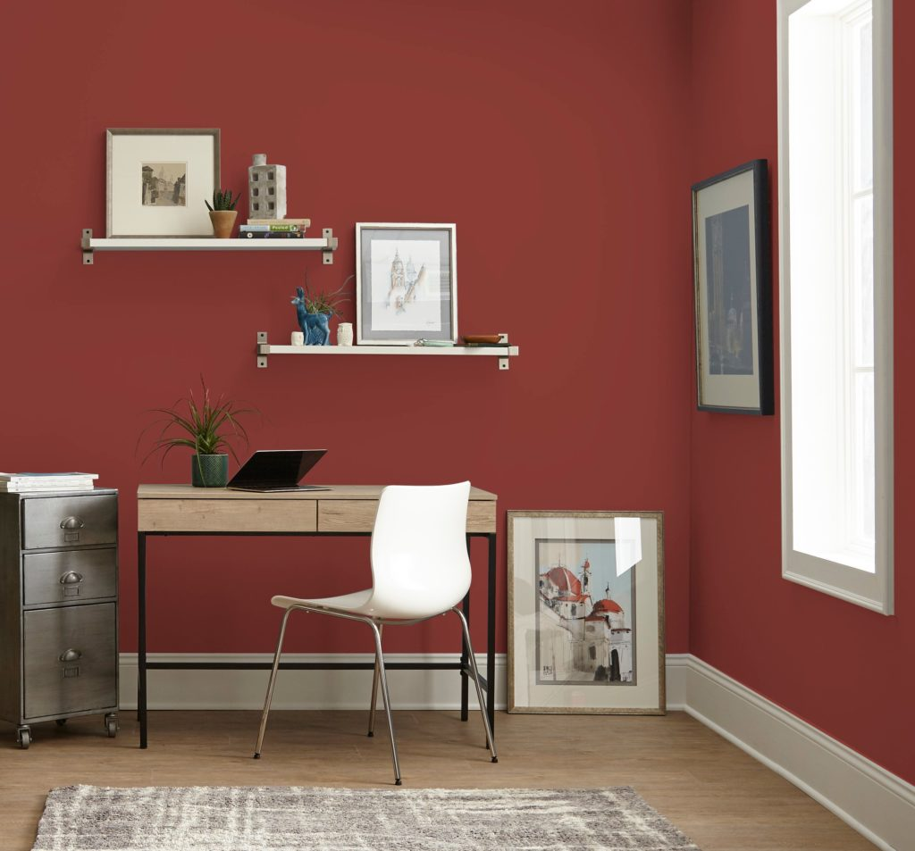A casual eclectic home office space, the walls are painted in a popular, deep red color called Red Pepper.