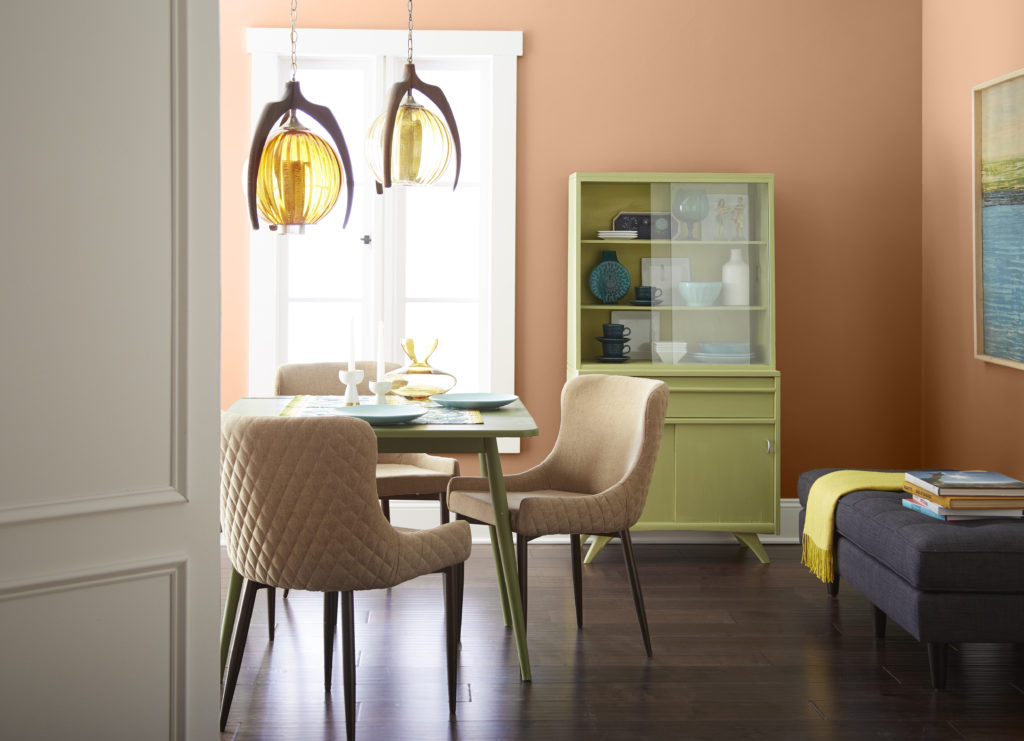 A mid-century dining room area with retro furniture pieces painted in bright pastel yellow-green color.  The terra cotta color on the wall coordinates nicely with the furniture keeping it from looking for bright but rather warm and welcoming.