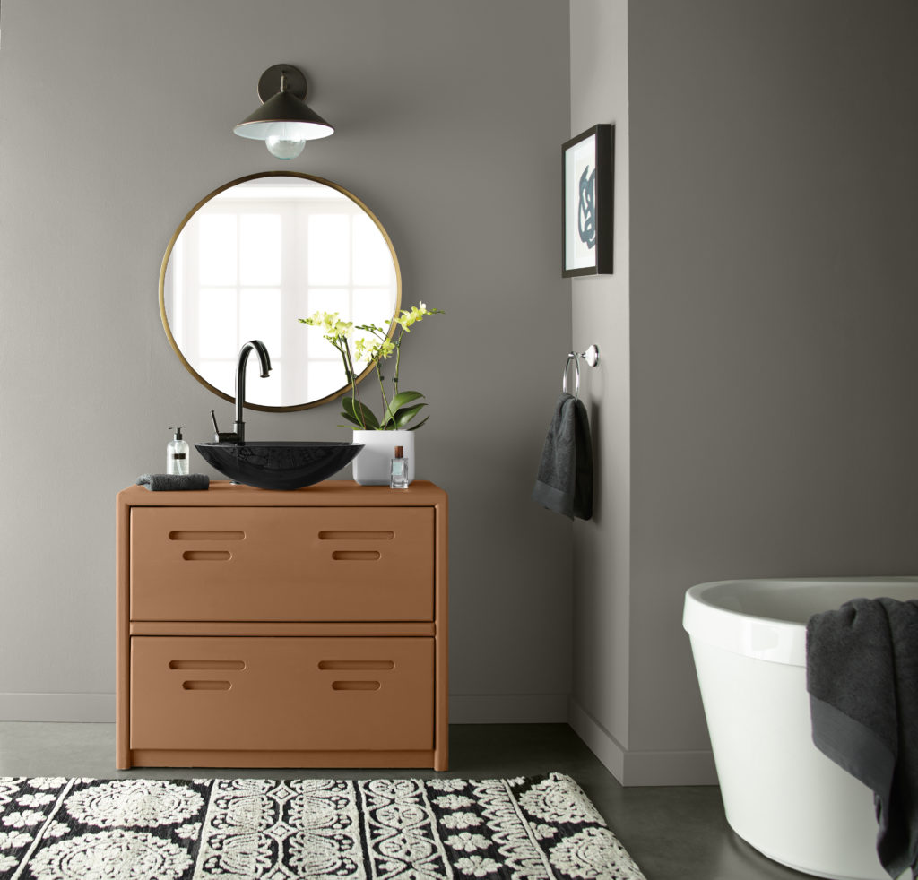 An eclectic gray bathroom with a round cotemporary  bath tub  and a unique and interesting vanity painted in an earthy orange color called Maple Glaze.