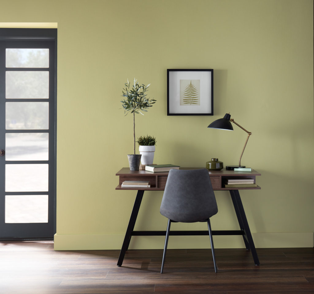 A simple desk work area.  There is a small desk with books, a chair, and a couple of plants.  The wall color is a mid-green with a yellow undertone called Back to Nature.