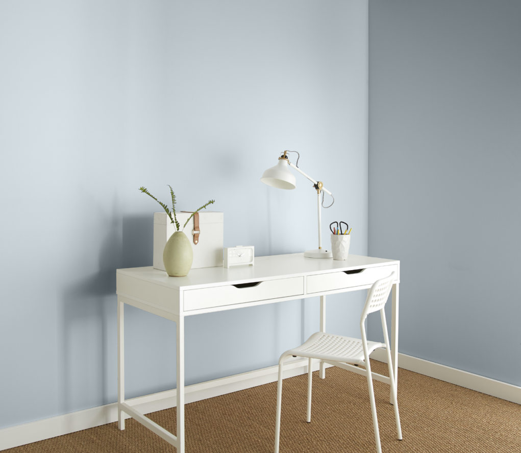 A simple home office featuring a light and airy blue color on the wall.  A white desk and chair with just a few desktop accessories.