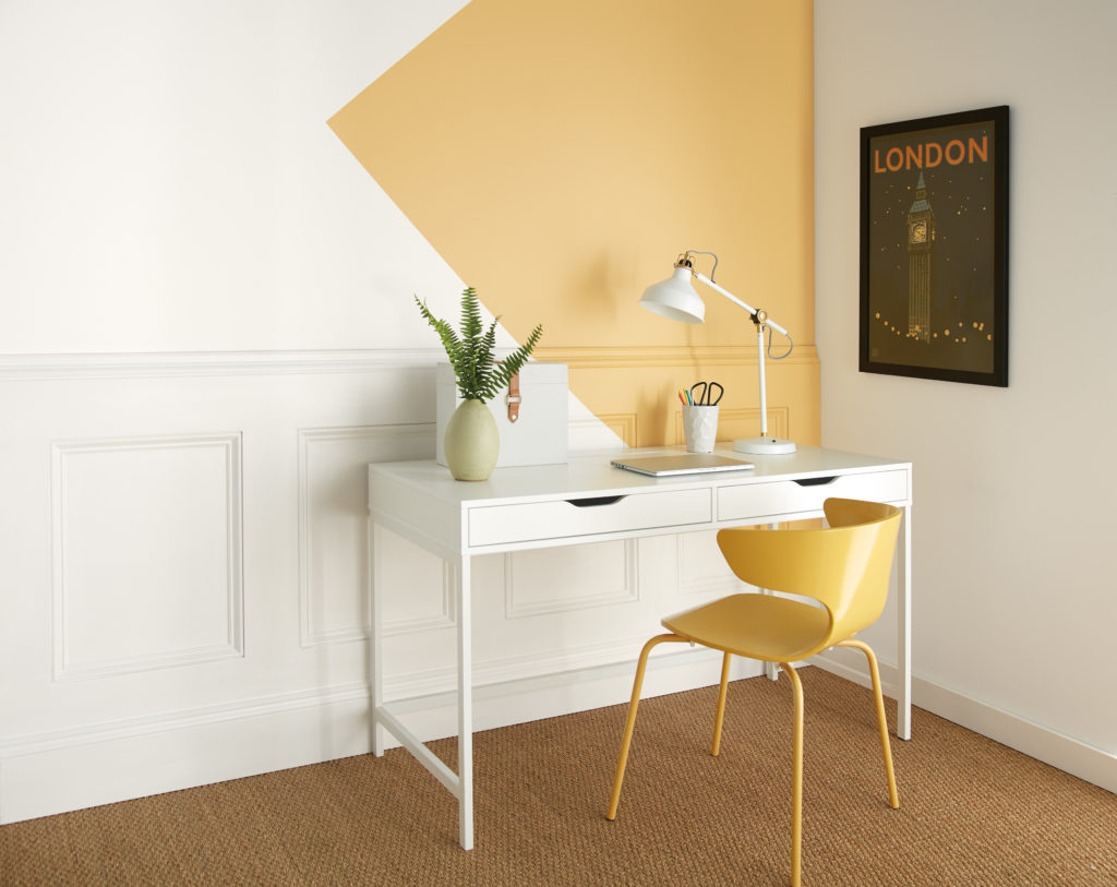 A simple deck area featuring a white walls with elegant wainscotting and a geometric paint design painted a mid yellow color.   A white desk and a yellow chair with just a few desktop accessories make the rest of this working corner.