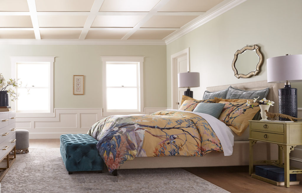 A large mastel bedroom painted in a sage green color called Jojoba.  The bedding has a floral pattern and the background color is a nice mid-tone which coordinated well with the green walls.  The ceiling has a paneling design and it is painted in  being and white colors.