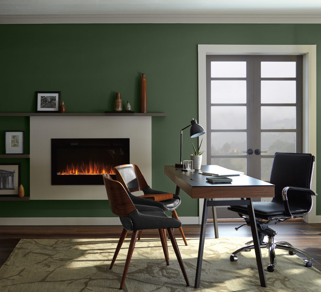 A contemporary home office painted in a dark green called Royal Orchard. The is and an adjustable black leather chair and two other chairs that create a conversation space.  The office space includes a fireplace and window with a beautiful vista.