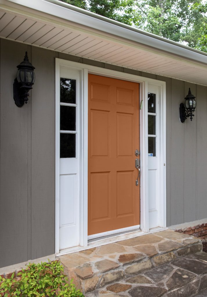 A mid range image of the front of a single family home.  The body of the house is painted in a mid-to-dark green with a green undertone called, Barnwood Gray.  The trim is featuring a super white color called ULTRA PURE WHITE.  The front main door features an inviting orange tone called Maple Glaze.