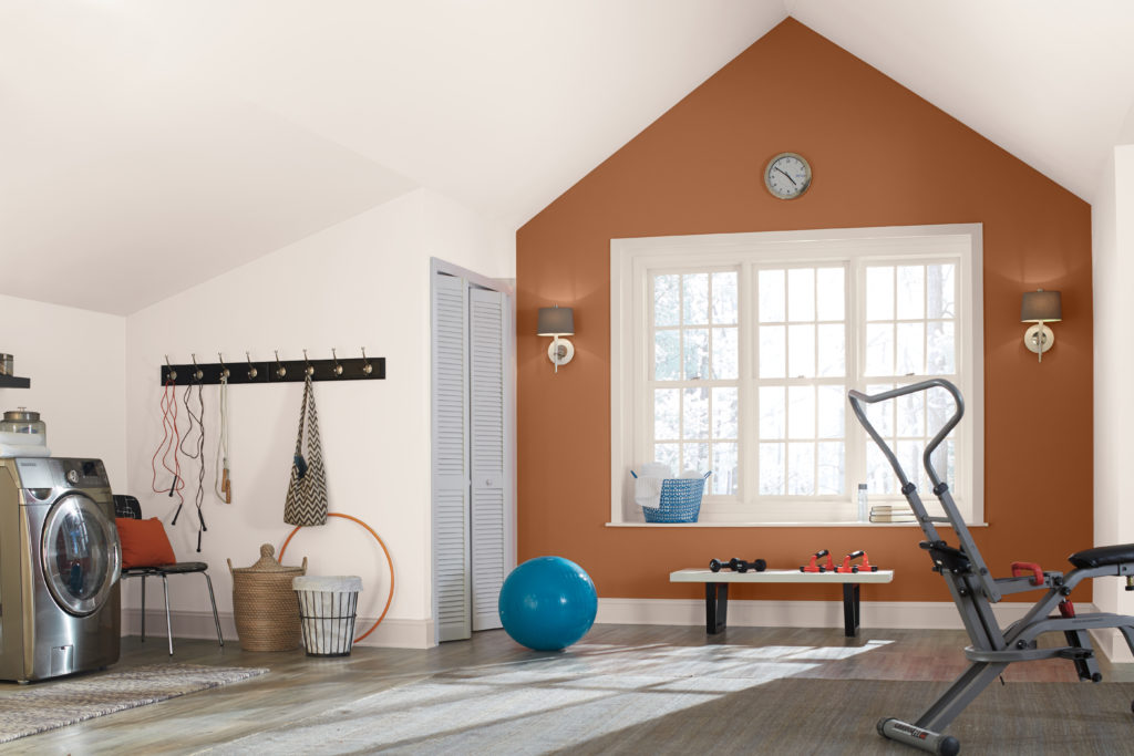 A large multi-purpose room  painted in a white color, there is a terra cotta color featured as an accent wall.   The accent color is called Maple Glaze and it helps highlight the architecture of this room.