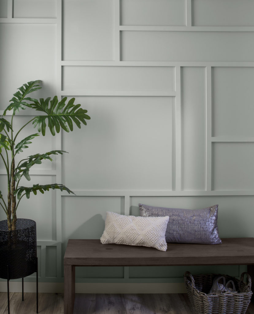 A close up view of a wall that has trim panelling added to create random rectangular and square shapes on a wall.