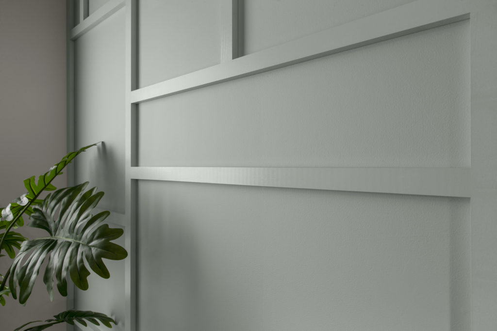 A close up view of a wall that has trim panelling added. The light is shining off of part of the trim to show how that the trim is a different sheen than the wall.