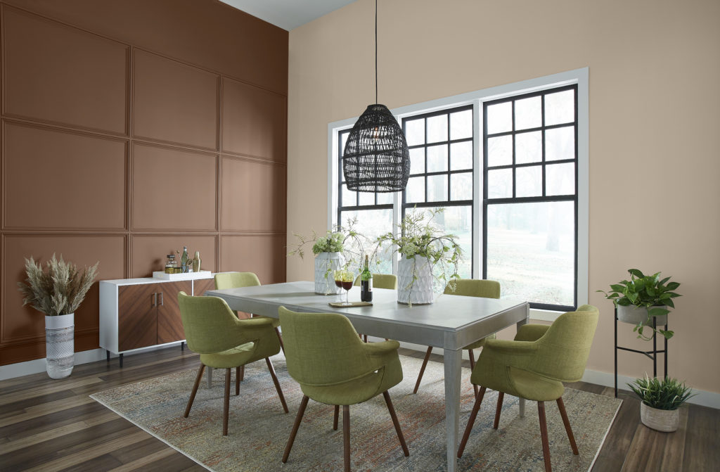 A modern dining room featuring a light gray dining table, apple green upholstered chairs.  The walls are being and dark brown.  The dark brown color is called Wild Mustang,  a gold-infused brown imparts mahogany richness and quiet strength.  The being color is called Studio Clay and it is a subtle sand tone captures both comfort and expansive appeal in a space.