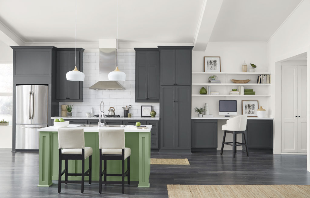 An expansive farmhouse style kitchen.   The walls and ceiling are white, the kitchen cabinets are painted in a dark gray color called Cracked Pepper, an authentic and reliable softened black offers infinite versatility.  The kitchen island is painted in a fresh herbal green color called, Laurel Tree.