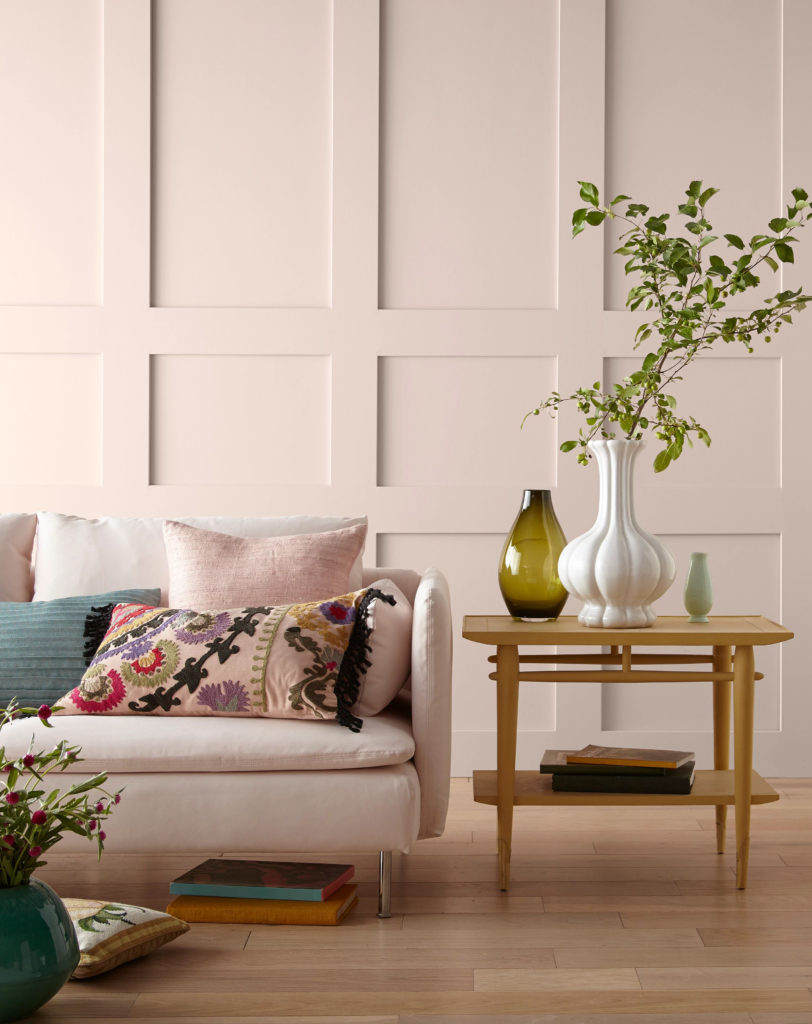 A living room with a decorative wall painted in a soft pink.