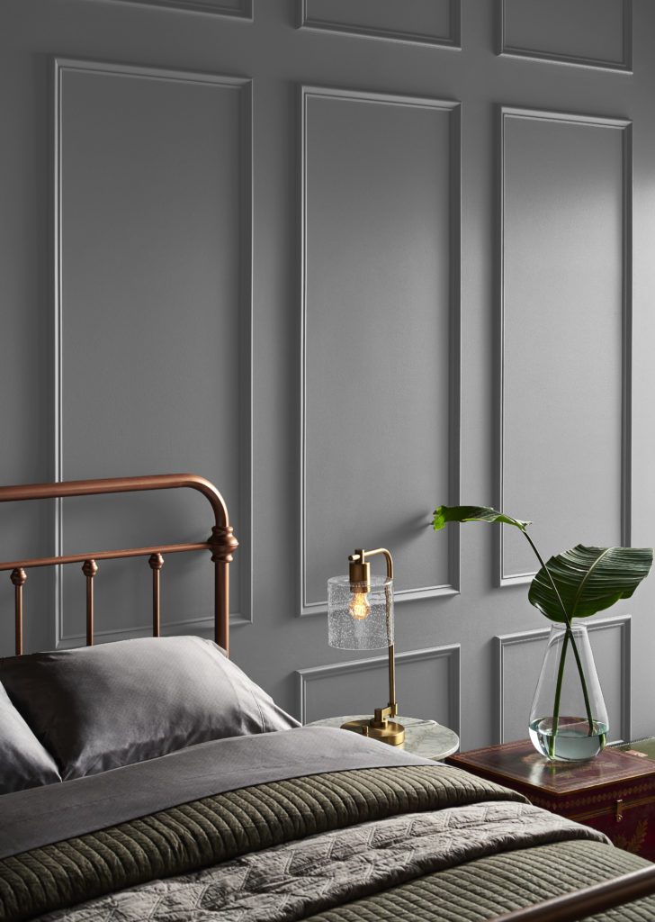 A bedroom with a decorative wall painted in a dark gray.