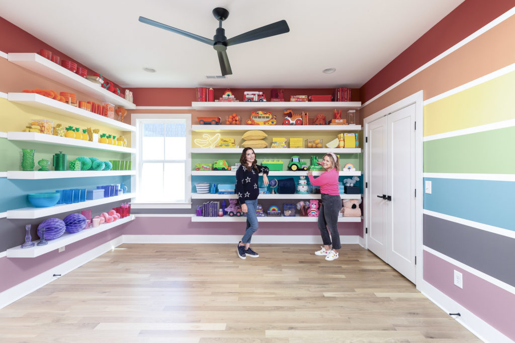 A room painted with a whimsical and colorful rainbow  in a vertical direction in all four walls of the room.  There are organizational open and free standing white shelves in two walls.  Clea and Joanna are standing intron of one set of shelves.