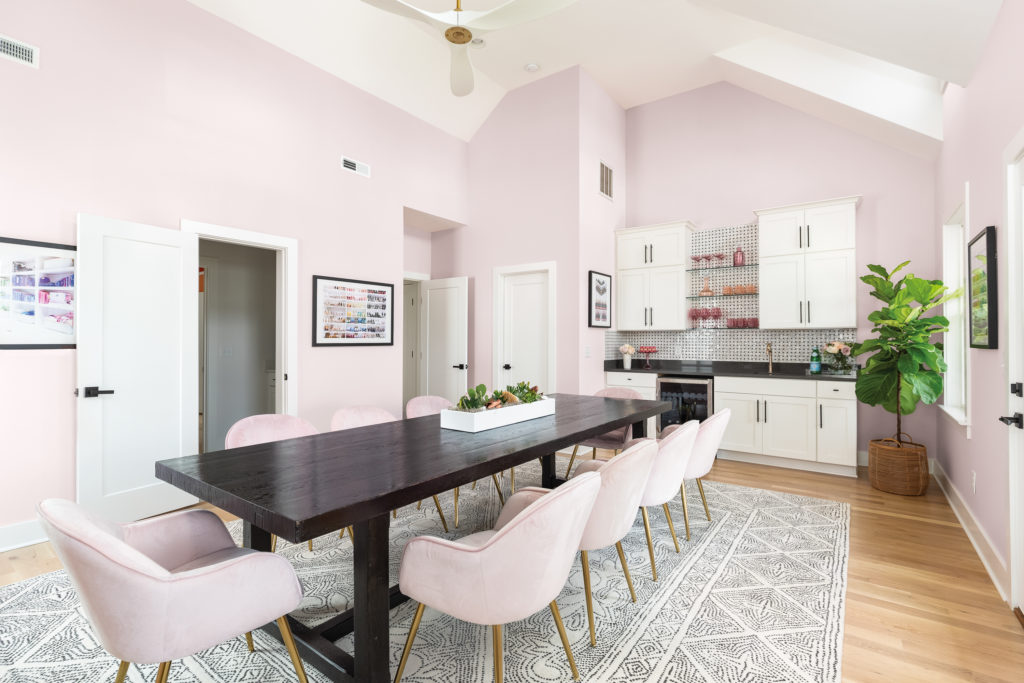 A large dining set and kitchenette room which serves as the teamwork and collaboration room. The room is painted in a light pink color called Moxie and the the ceiling is high and white with a white fan.