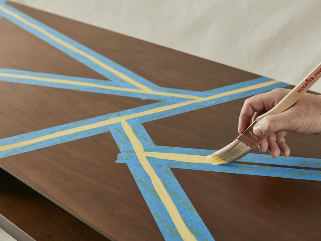 A person painting yellow lines on top of a stained coffee table.