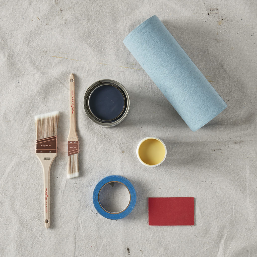 showing product and tools needed for a project; stain, paint, bruchses, sandpaper, painters tape, rags.
