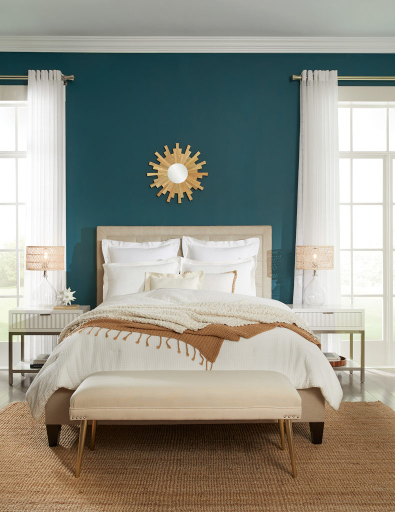 A bedroom with dark  teal color walls and white trim and ceiling, the color used on the wall is called Ocean Abyss.  The bedroom is dresses in off white neutral bedding and a brown accent blanket.